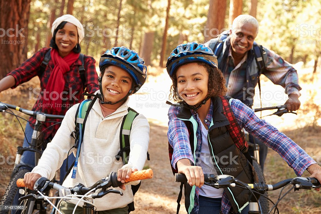 Grandparents With Children Cycling Through Fall Woodland stock photo