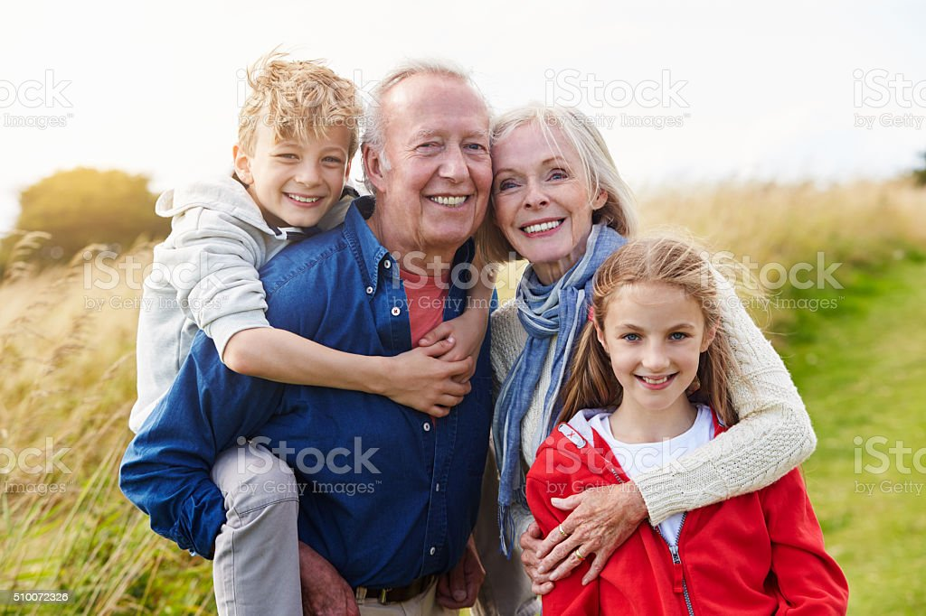 Grandparents With Children On Walk Through Countryside stock photo
