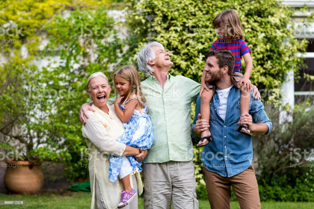 Grandparents with grandchildren and son standing in yard stock photo
