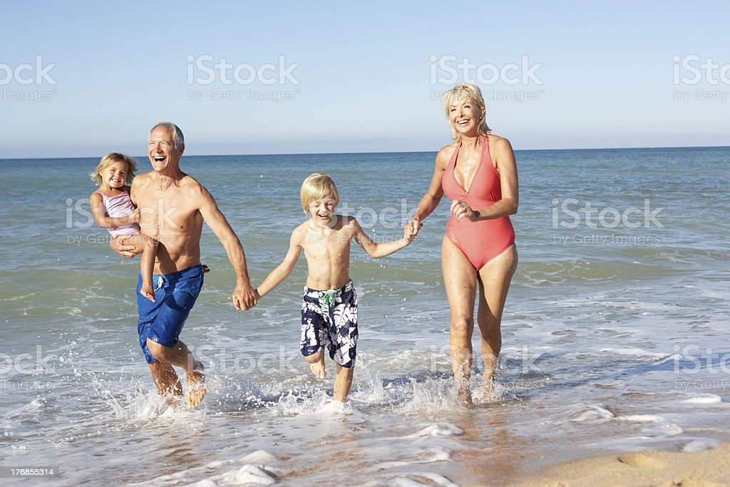 Grandparents With Grandchildren Enjoying Beach Holiday Together royalty-free stock photo