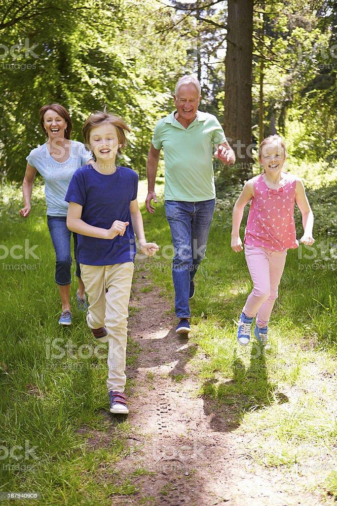 Grandparents With Grandchildren Running Through Countryside stock photo