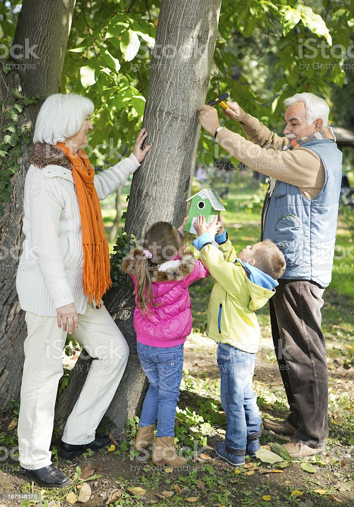 Grandparents with grandchildren walking in park. royalty-free stock photo