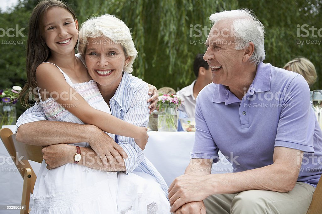 Grandparents With Granddaughter At Table In Garden royalty-free stock photo