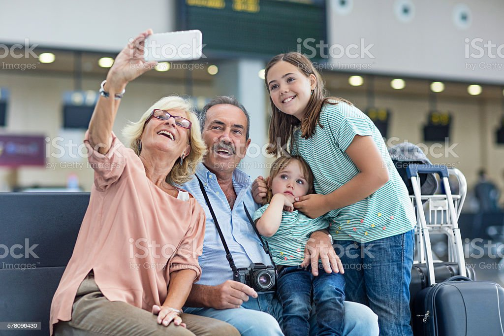 Grandparents with granddaughters taking a selfie in the airport stock photo