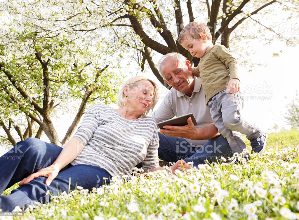 Grandparents with grandson enjoying the sunny spring day. stock photo