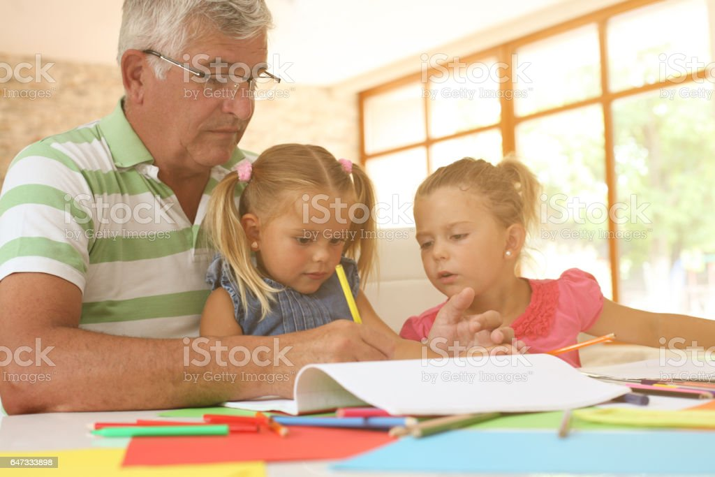 Grandparents working homework with granddaughters. stock photo