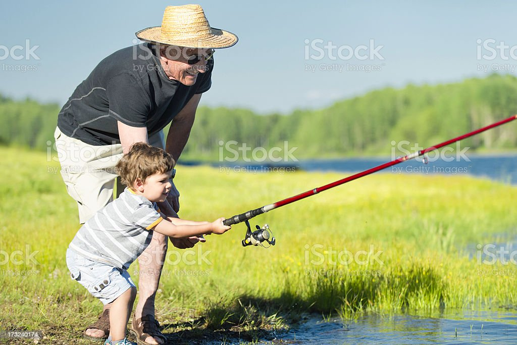 Grandson and grandfather fishing royalty-free stock photo
