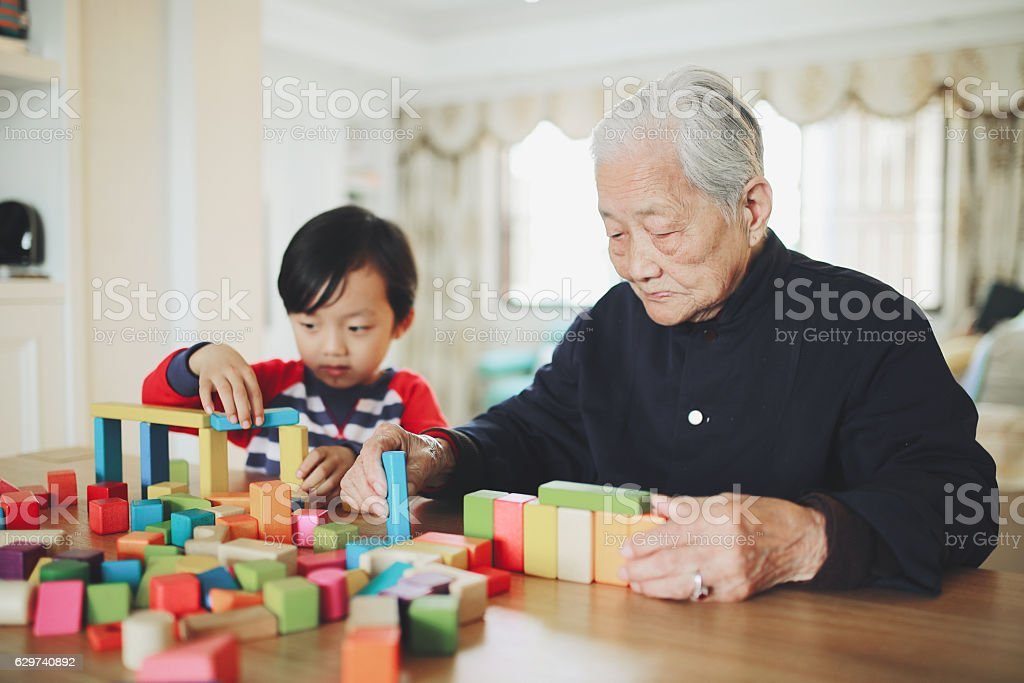Grandson and grandma playing with blocks stock photo
