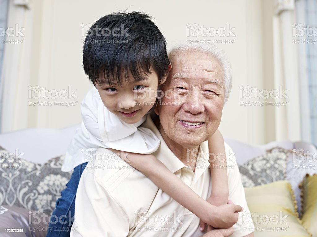 A grandson and grandpa smiling at the camera royalty-free stock photo