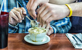 Grandson Helping Grandfather Crumble Crackers Into Cup of Vegetable Soup