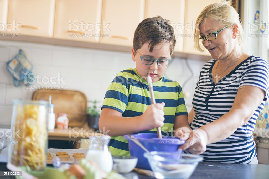 Grandson Helping Grandmother To Bake coockies In Kitchen stock photo