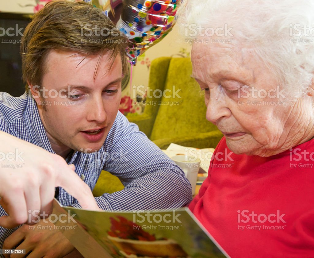 Grandson helps his Grandmother read her birthday card stock photo