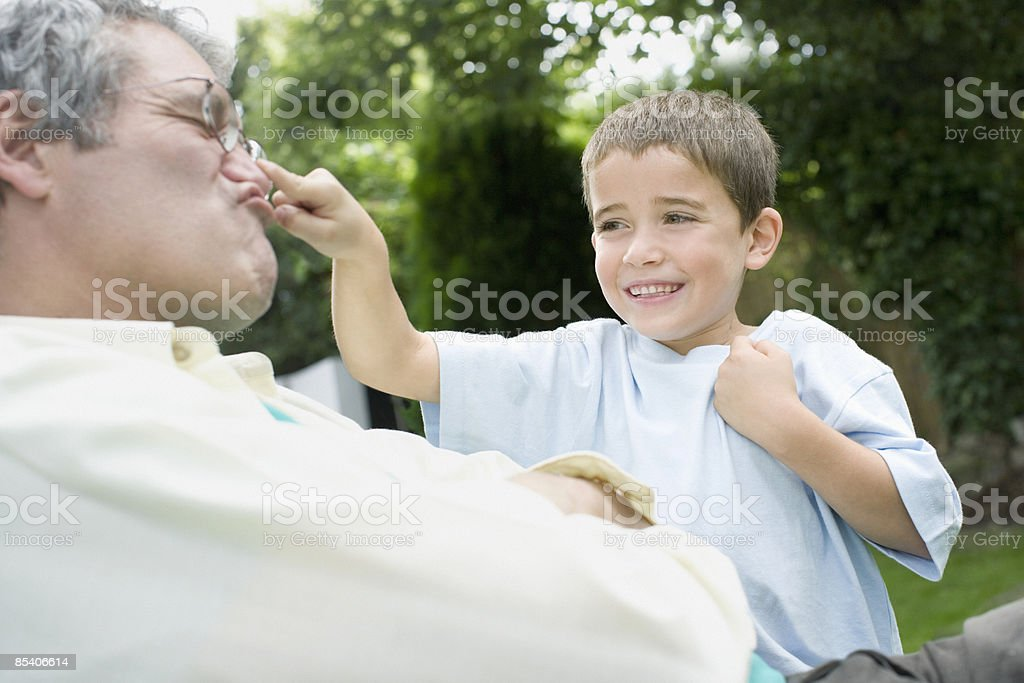 Grandson playing with grandfathers nose stock photo