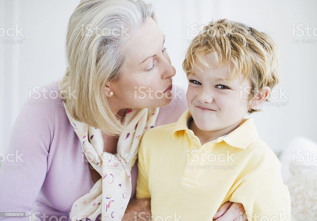 Grandson refusing grandmothers kiss stock photo