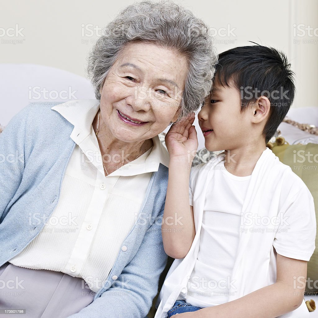 Grandson whispering into his grandmas ear royalty-free stock photo
