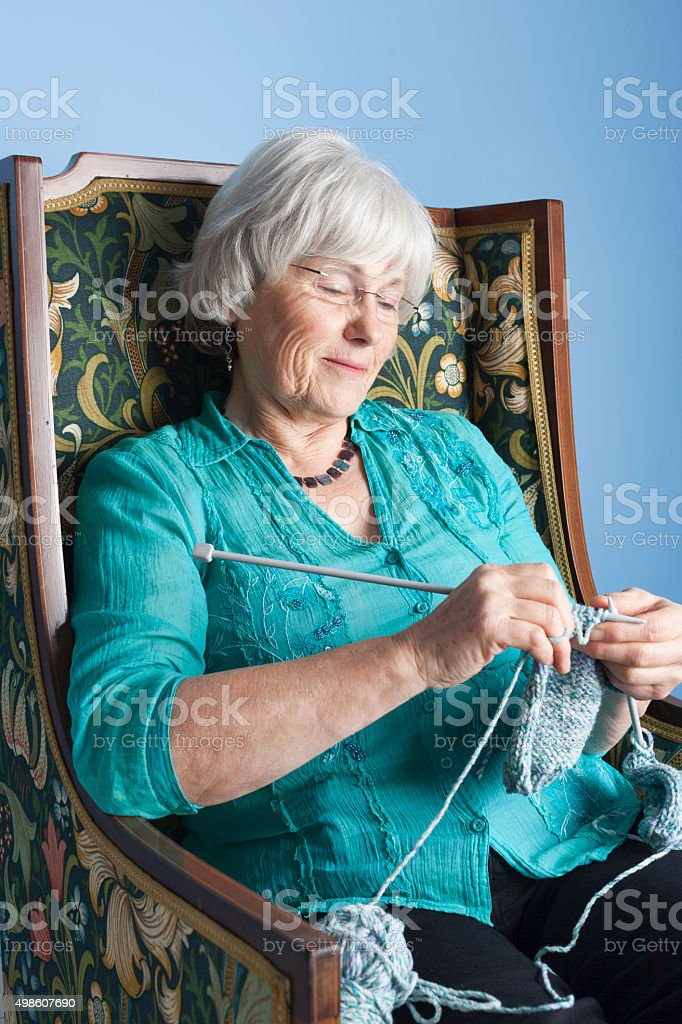 Grannie Knitting In Her Favourite Chair stock photo