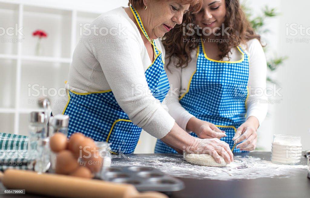 Granny and granddaughter preparing bread stock photo