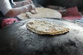 Granny chef cook Turkish pancake Gozleme on the stove