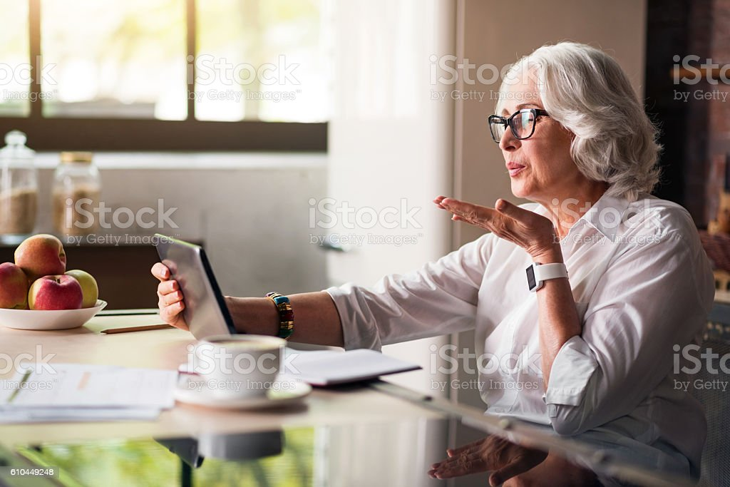 Granny communicating with her family via skype stock photo
