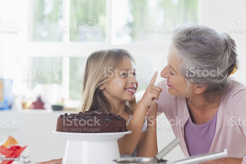 Granny having fun with granddaughter icing a cake stock photo