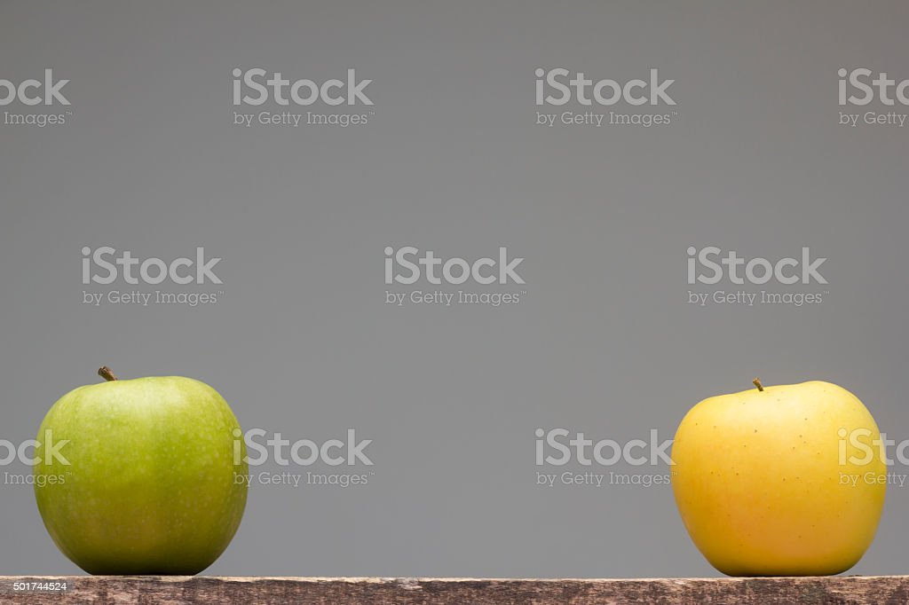 Granny smith and golden delicious apples isolated on wooden table stock photo