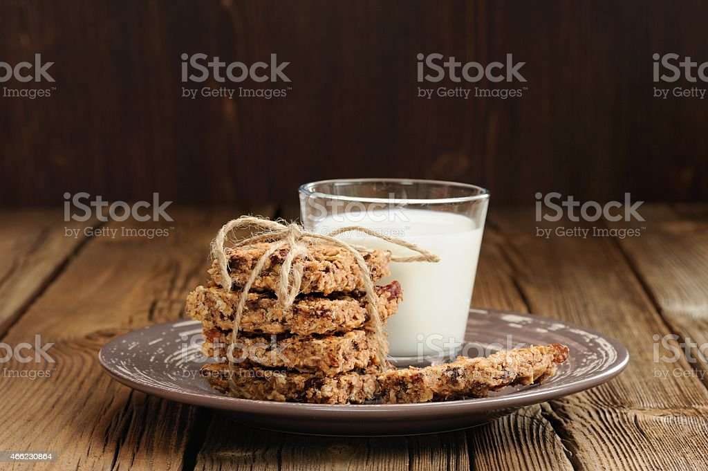 Granola bars with glass of milk on wooden background stock photo