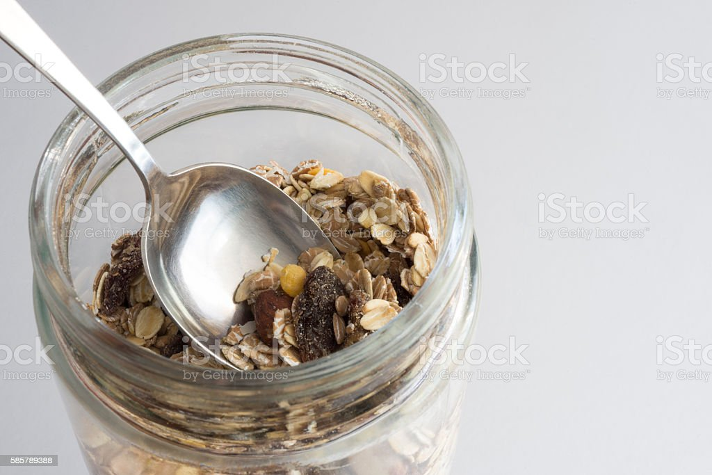 Granola in a glass container with a spoon stock photo