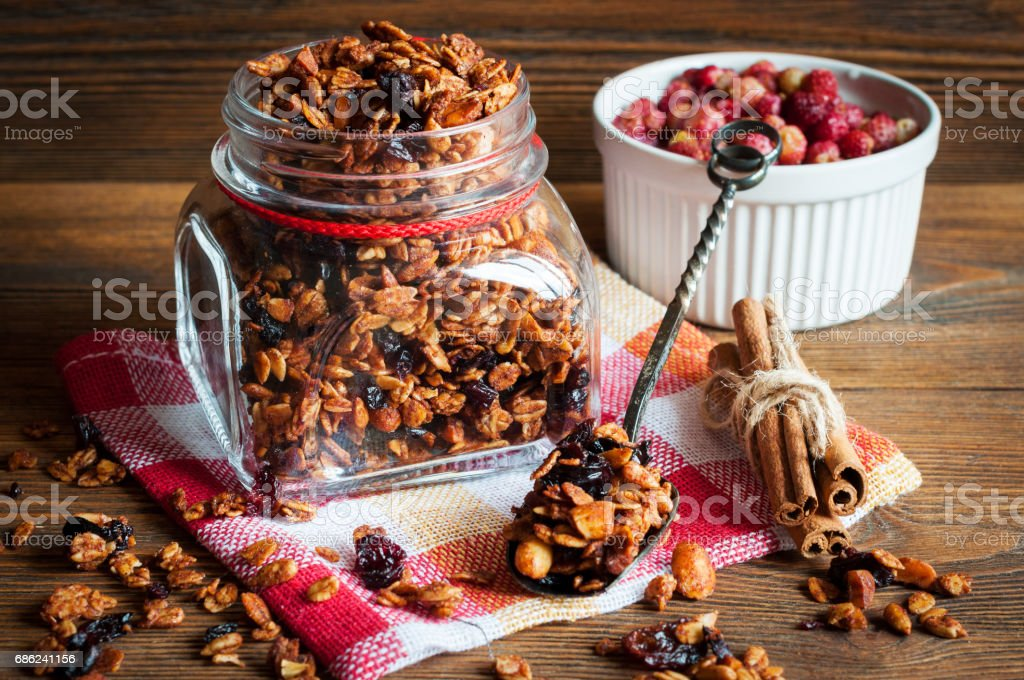 Granola in open glass jar and wild  strawberries stock photo