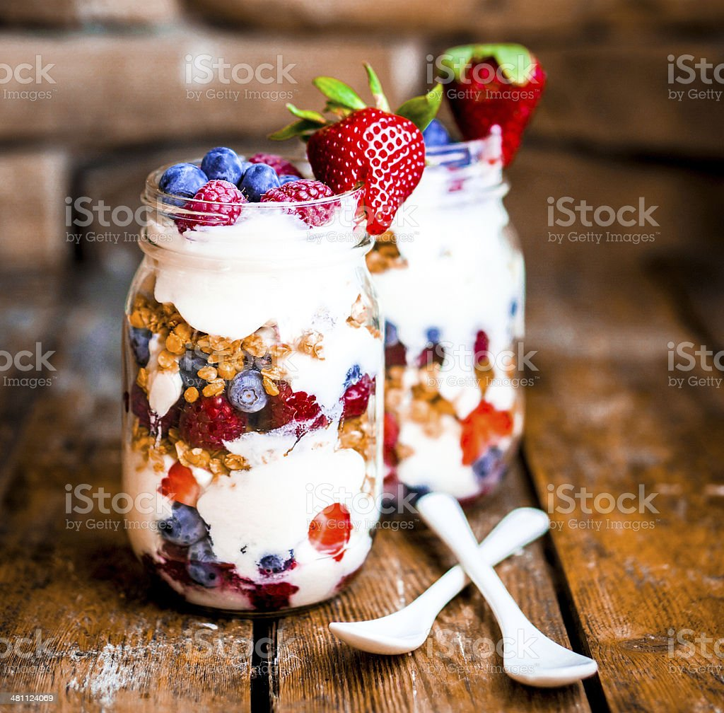 Granola Parfait with yogurt and berries on rustic background stock photo