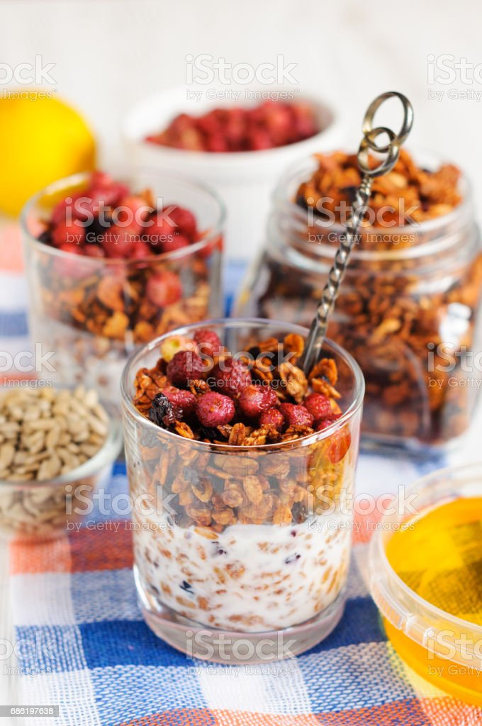 Granola with berries and yogurt in glasses stock photo