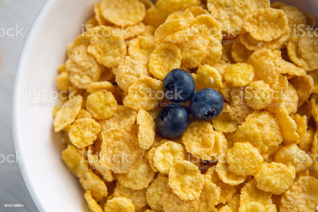 granola with blueberries in white bowl on wooden stock photo