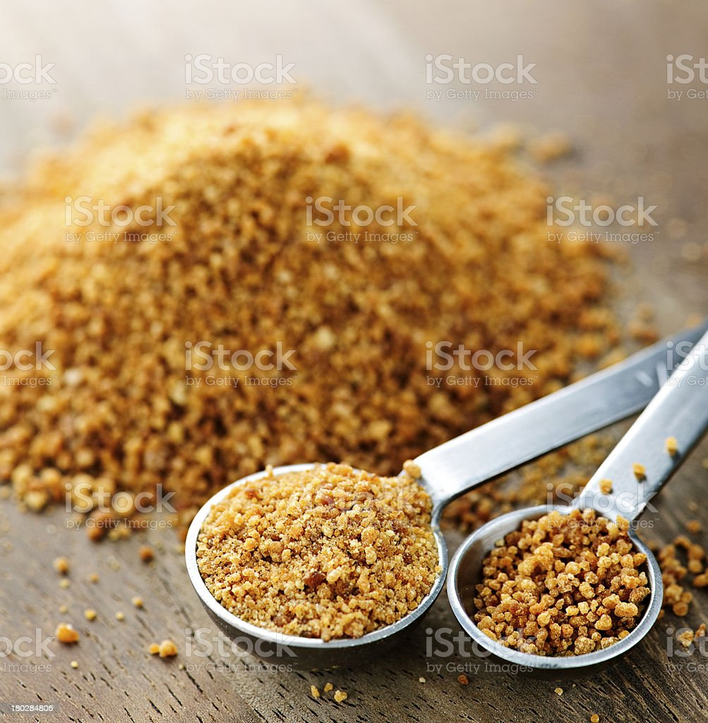 Granulated coconut palm sugar in measuring spoons on table royalty-free stock photo