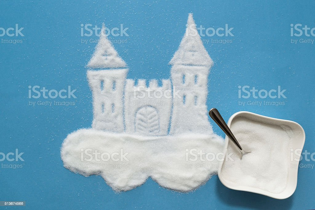 granulated sugar castle on blue background stock photo