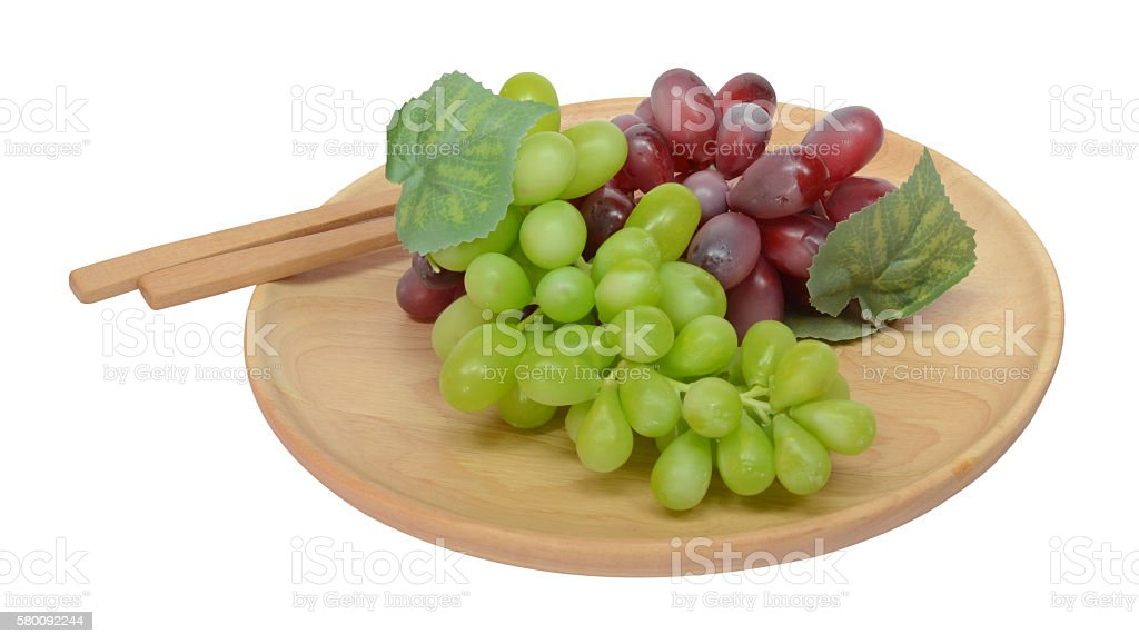 Grape in a wooden plate and wooden column with paths zbiór zdjęć royalty-free
