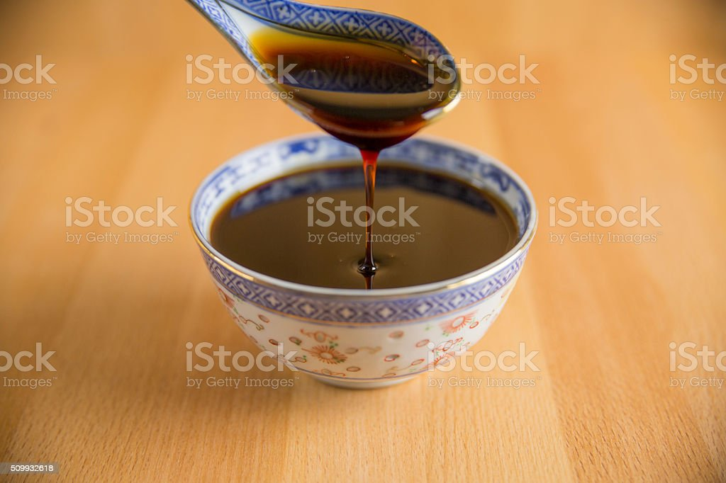 Grape molasses flowing from the spoon on wooden background. stock photo