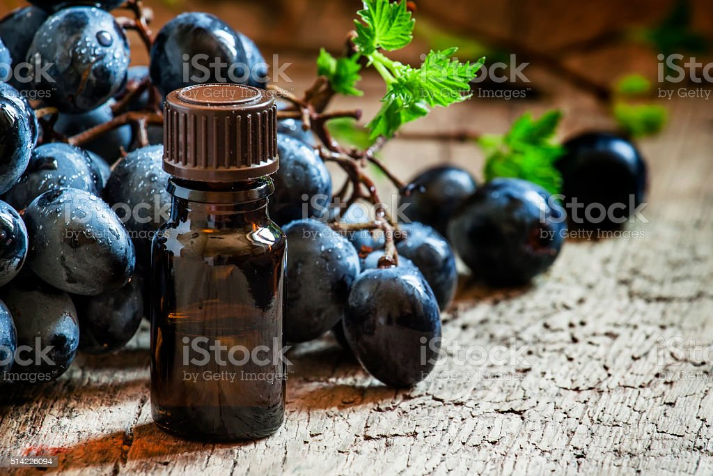 Grape seed oil in brown bottle, bunch of grapes, vine stock photo