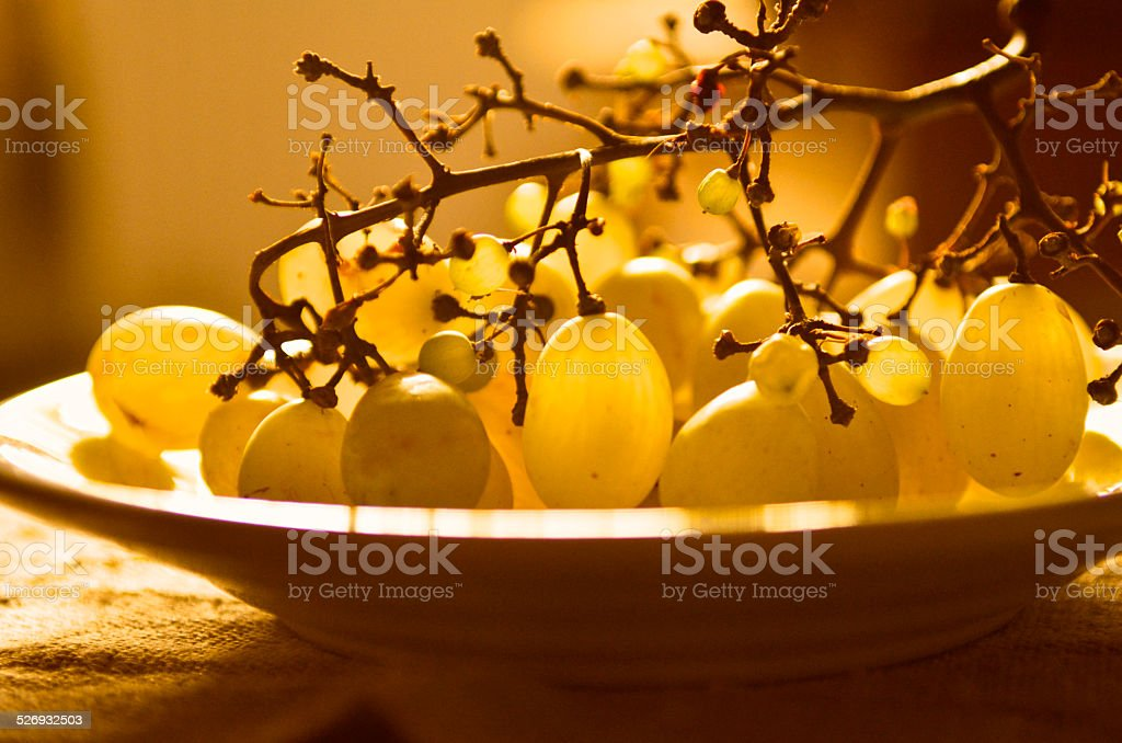 grape stalk with fruits in plate, back gold light stock photo