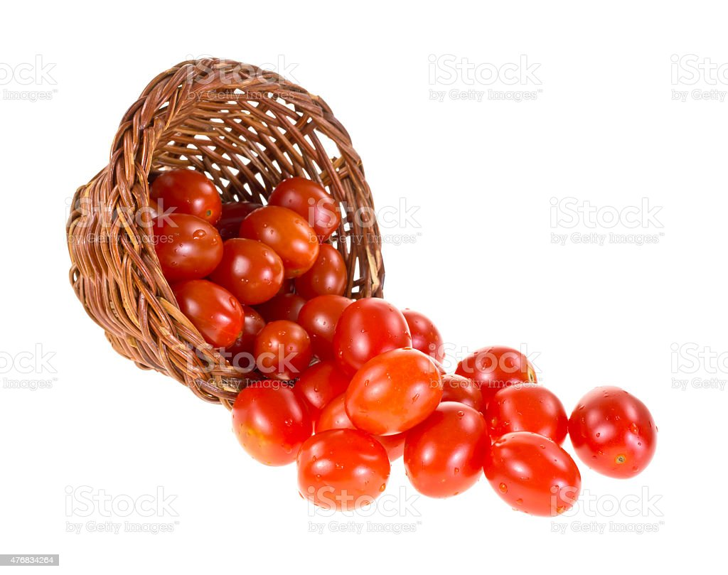 Grape tomatoes spilling from basket stock photo