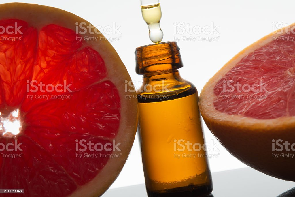 Grapefruit essential oil in amber glass with dropper stock photo