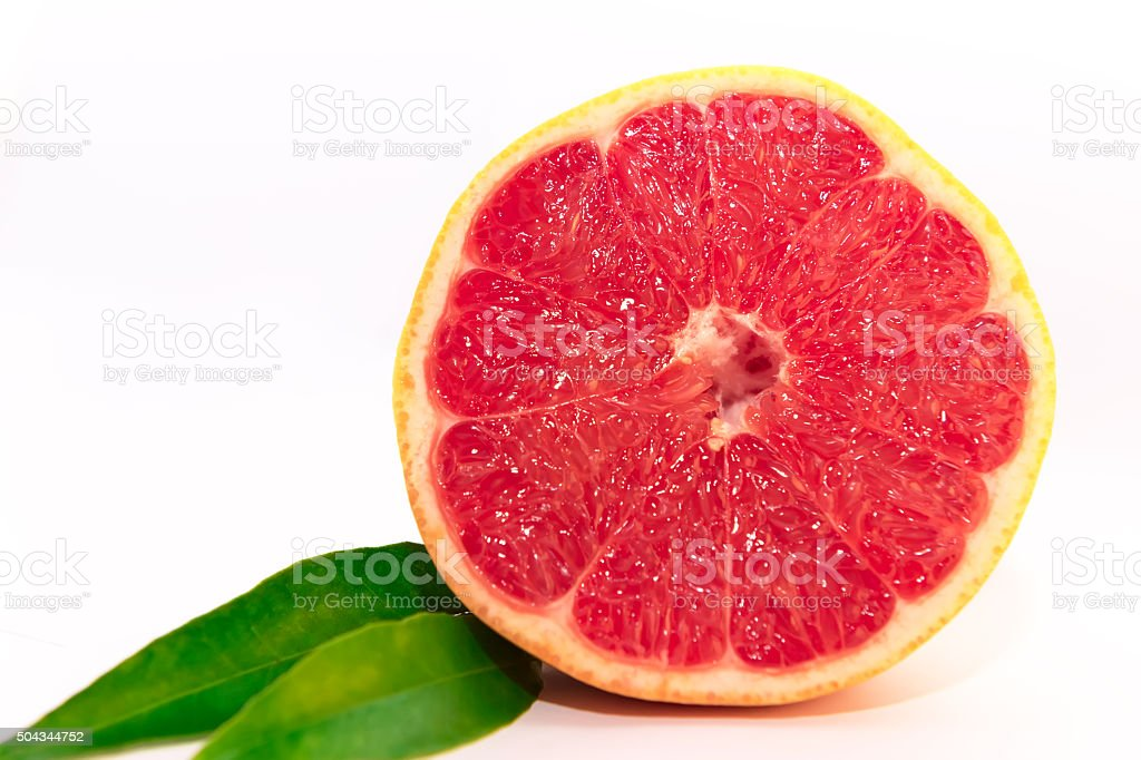 Grapefruit halves with green leaf isolated on white background stock photo