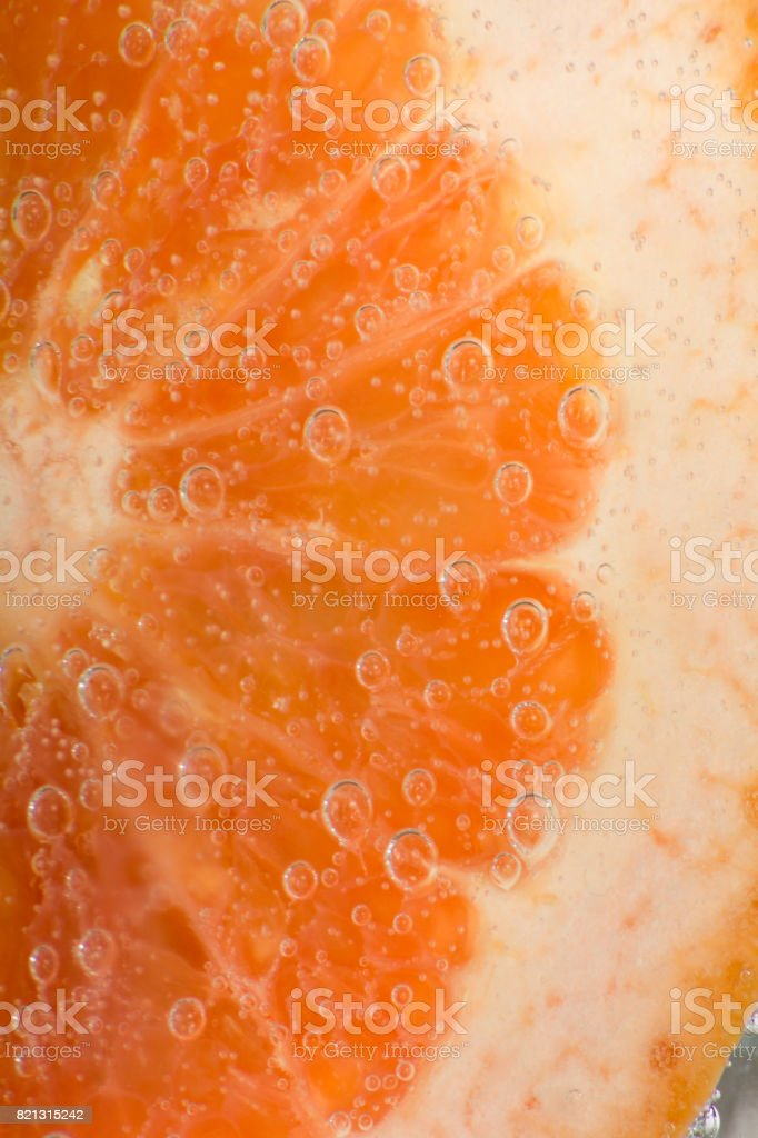 Grapefruit Slice with Bubbles in Soda Water stock photo