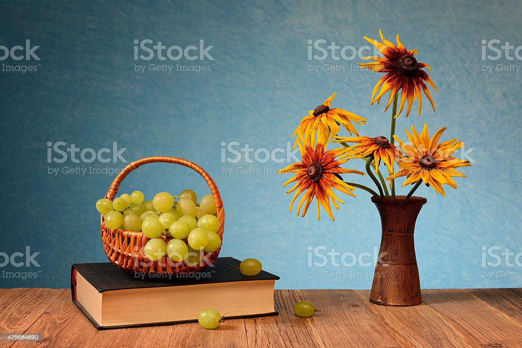 Grapes in wicker baskets and flowers in a vase stock photo