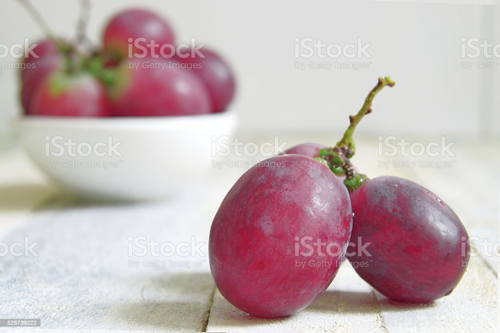 Grapes on a white wooden table of a rustic kitchen. stock photo