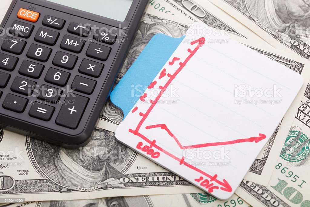 Graph and calculator on money background stock photo