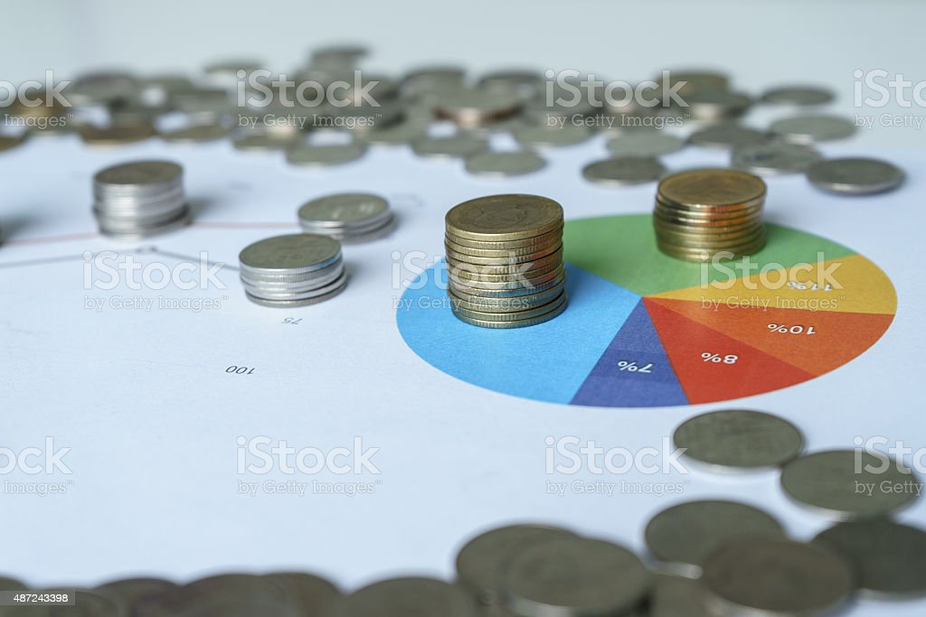 Graph and money coins on the table stock photo