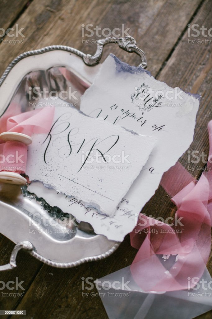 Graphic arts of beautiful wedding calligraphy cards and silver plate with silk ribbon. stock photo