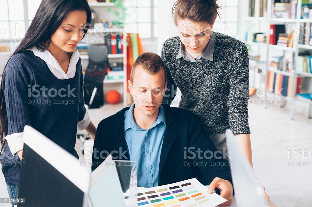 Graphic designer and his assistants at workplace stock photo