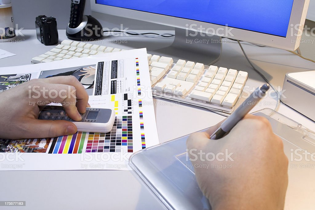 Graphic designer at work. Schedule checks the colors on the printout. stock photo