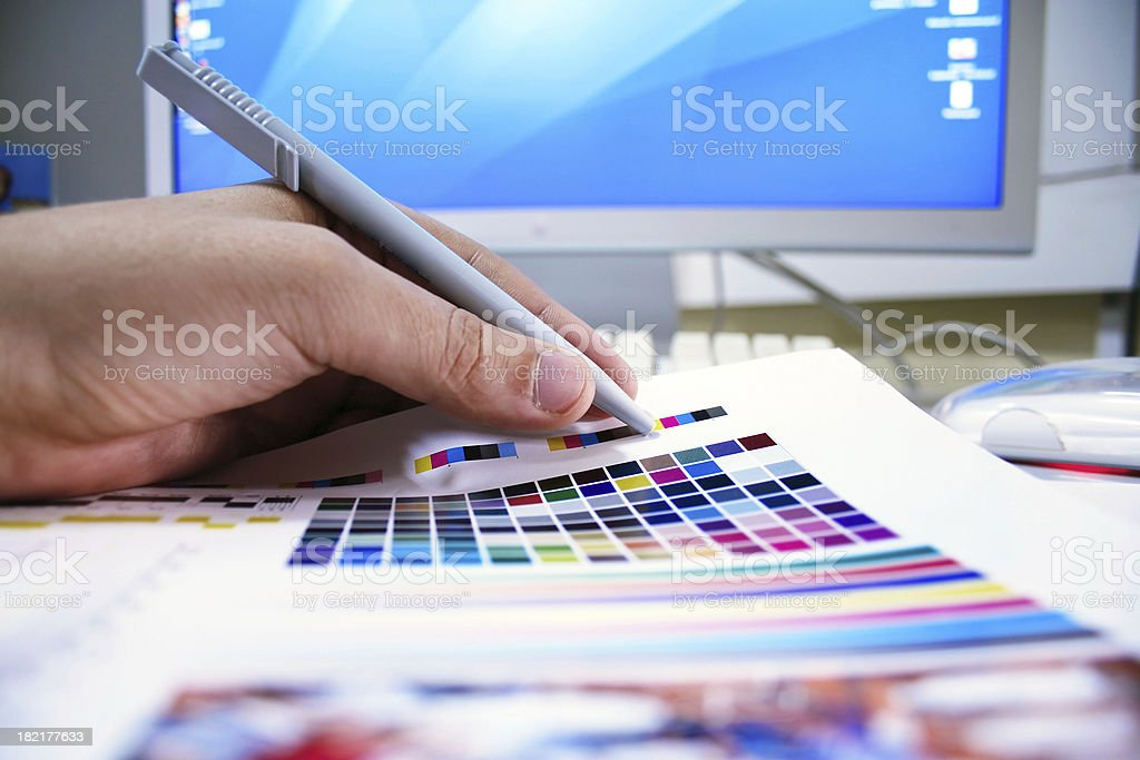 Graphic designer checks the colors on the printed page royalty-free stock photo