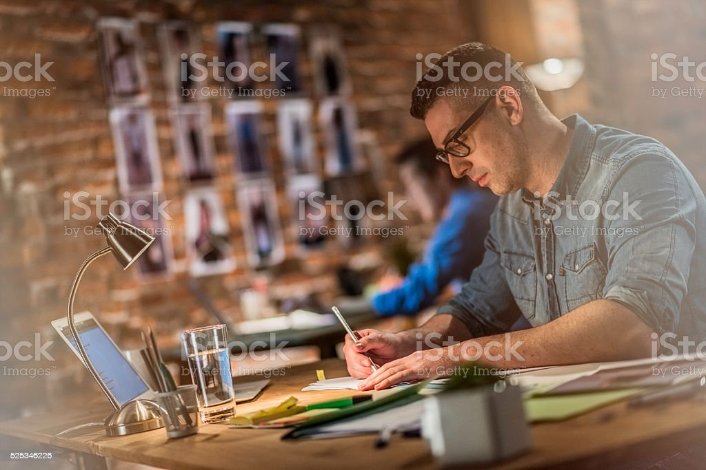 Graphic designer making sketches behind a desk stock photo
